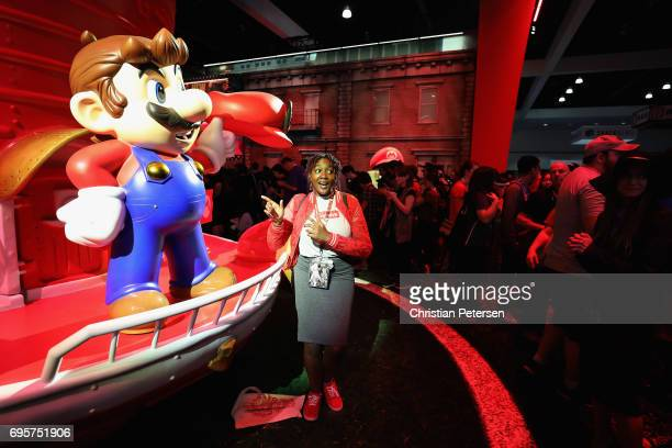 Attendee Mia Watkins poses with 'Super Mario' while visiting the Nintendo exhibit during the Electronic Entertainment Expo E3 at the Los Angeles...