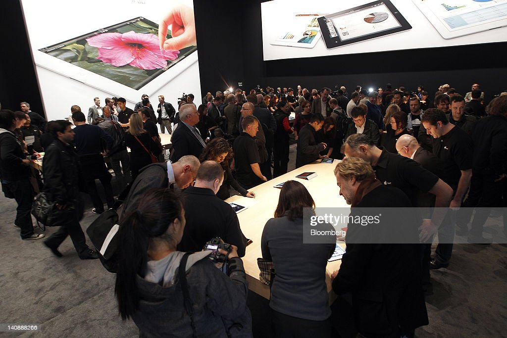 Attendees and members of the media view Apple Inc.'s new version of the iPad tablet computer after its unveiling at an Apple event in San Francisco, California, U.S., on Wednesday, March 7, 2012. Apple Inc. introduced a new version of the iPad, beefing up its two-year-old mobile computer with a sharper screen to widen its lead over Amazon.com Inc., Microsoft Corp. and Google Inc. in the tablet market. Photographer: Tony Avelar/Bloomberg via Getty Images