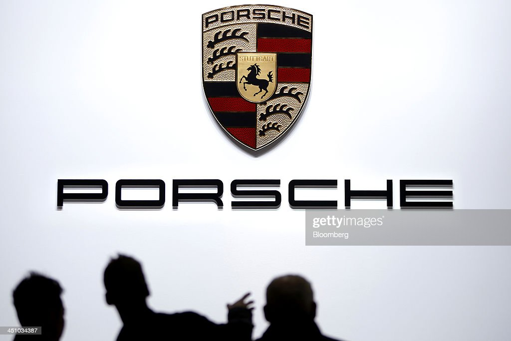 Attendees are silhouetted against a wall displaying the Porsche SE logo at the 43rd Tokyo Motor Show 2013 in Tokyo, Japan, on Thursday, Nov. 21, 2013. The autoshow will be open to the public from Nov. 23 to Dec. 1 at the Tokyo International Exhibition Center, also known as the Tokyo Big Sight. Photographer: Kiyoshi Ota/Bloomberg via Getty Images