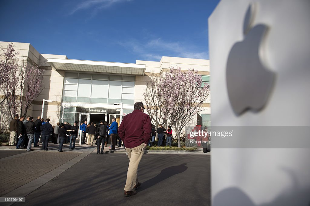 Attendees arrive at the Apple Inc. shareholders meeting at the company's headquarters in Cupertino, California, U.S., on Wednesday, Feb. 27, 2013. As Apple Inc. Chief Executive Officer Tim Cook takes the stage at this year's shareholder meeting, he may not get the reception he received in 2012, when investors lauded the company's performance and rising shares. Photographer: David Paul Morris/Bloomberg via Getty Images