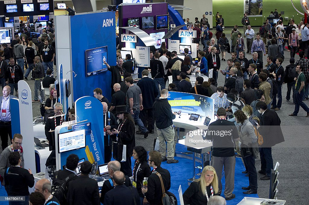 Attendees at the Arm Holdings Plc and Intel Corp. booths at the Game Developers Conference 2013 in San Francisco, California, U.S., on Wednesday, March 27, 2013. With over 22,500 attendees, the Game Developers Conference is the world's largest and longest-running professionals-only game industry event. Photographer: David Paul Morris/Bloomberg via Getty Images