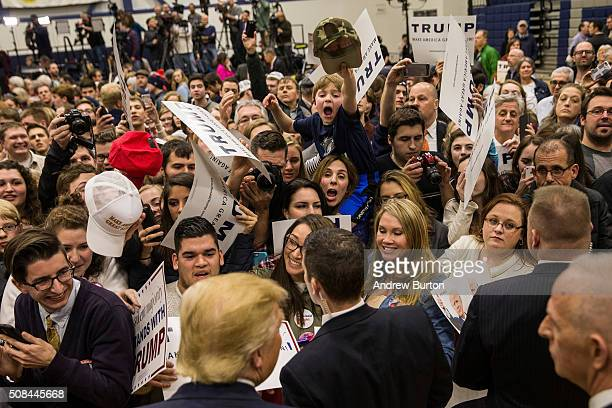 Attendees attempt to meet Republican presidential hopeful Donald Trump at the end of a rally at Great Bay Community College on February 4 2016 in...