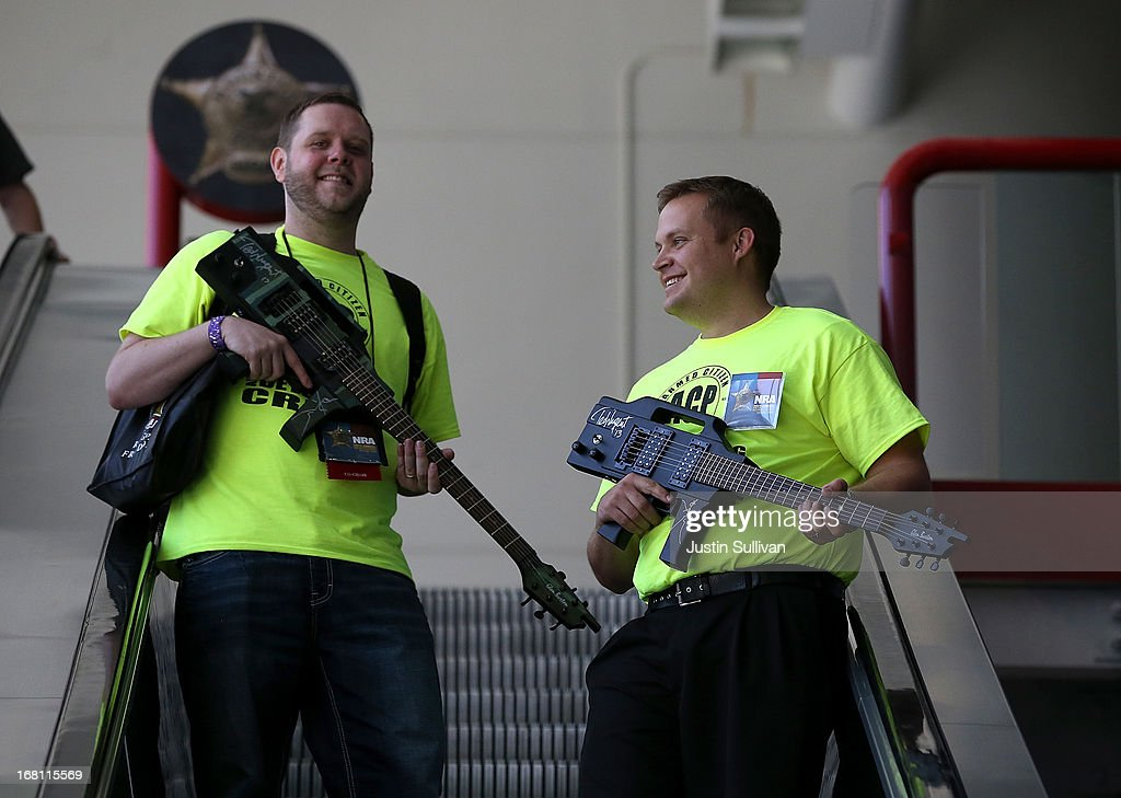 Attendees carry guitars that look like assault rifles as they ride an escalator during the 2013 NRA Annual Meeting and Exhibits at the George R. Brown Convention Center on May 5, 2013 in Houston, Texas. More than 70,000 people attended the NRA's 3-day annual meeting that featured nearly 550 exhibitors, a gun trade show and a political rally.