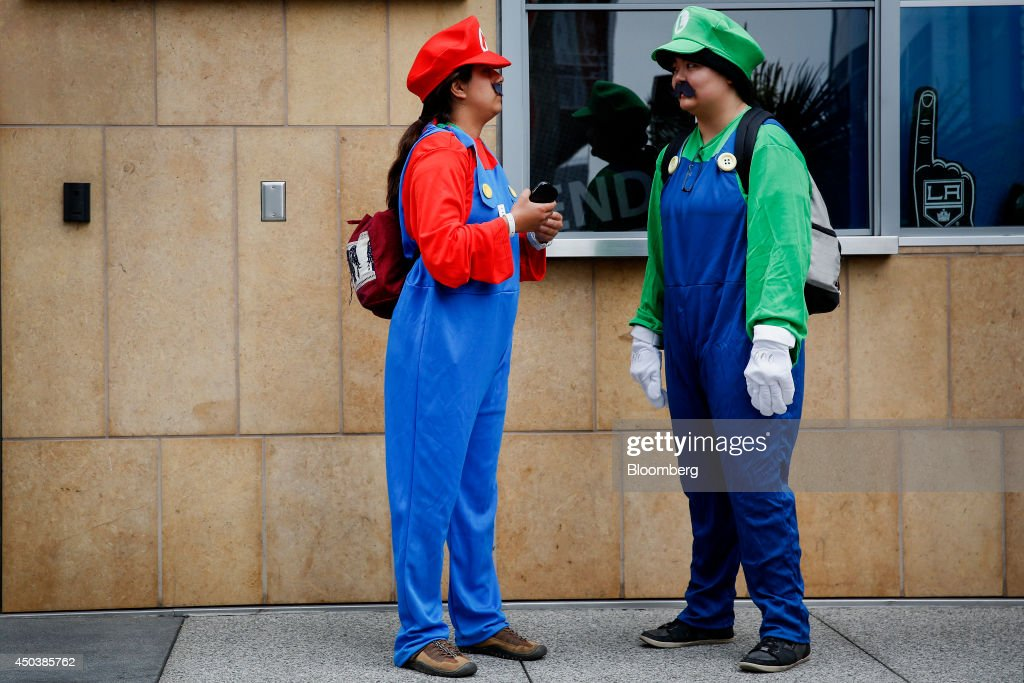 Attendees Della Martinez, left, and Sarah Kim, dressed in costume as Nintendo Co.'s Mario and Luigi, wait for the start of the E3 Electronic Entertainment Expo in Los Angeles, California, U.S., on Tuesday, June 10, 2014. E3, a trade show for computer and video games, draws professionals to experience the future of interactive entertainment as well as to see new technologies and never-before-seen products. Photographer: Patrick T. Fallon/Bloomberg via Getty Images