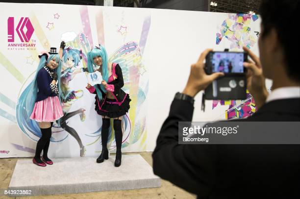 Attendees dressed as Hatsune Miku a virtual pop star and the voice behind Crypton Future Media Inc's vocal synthesizer software pose for a photograph...