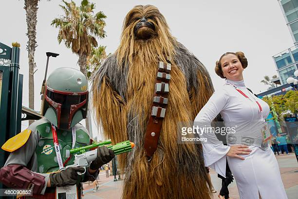 Attendees dressed as 'Star Wars' characters Boba Fett Chewbacca and Princess Leia stand for a photograph during the ComicCon International convention...
