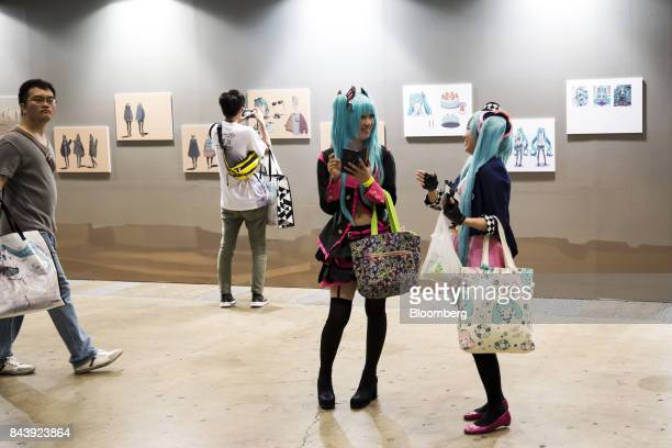 Attendees dresses as Hatsune Miku a virtual pop star and the voice behind Crypton Future Media Inc's vocal synthesizer softwaretalk during the...
