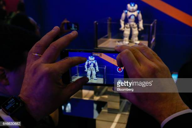 Attendees film a NAO humanoid robot developed by Softbank Corp subsidiary Aldebaran Robotics SA on the third day of Mobile World Congress in...