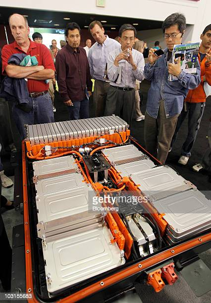 Attendees gather around Nissan Leaf lithiumion batteries on display at the PlugIn 2010 event in San Jose California US on Tuesday July 27 2010 Nissan...
