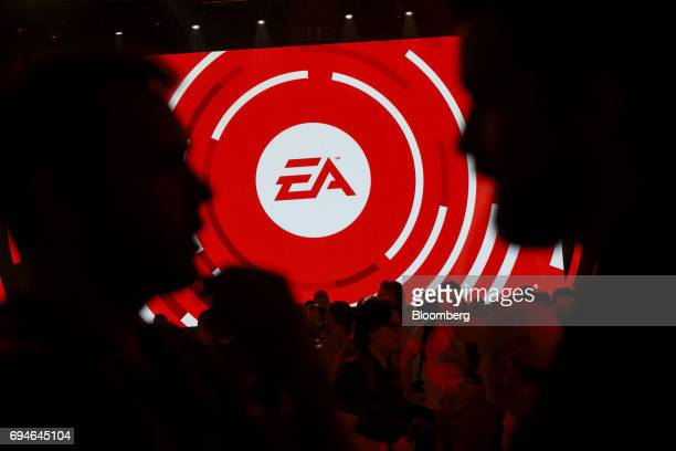Attendees gather in front of an Electronic Arts Inc logo displayed on a screen during the company's EA Play event ahead of the E3 Electronic...