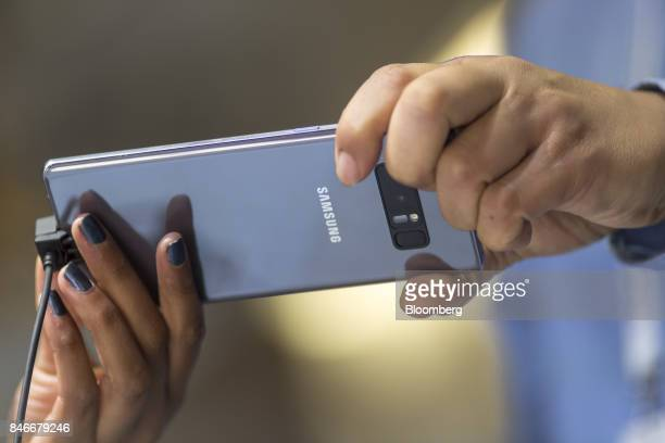 Attendees hold a Samsung Electronics Co Galaxy Note 8 smartphone displayed at the Mobile World Conference Americas event in San Francisco California...