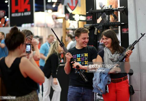 Attendees hold assault rifles as they pose for a photo during the 2013 NRA Annual Meeting and Exhibits at the George R Brown Convention Center on May...