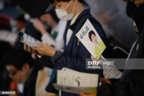 Attendees hold campaign pamphlets featuring an image of Yuriko Koike governor of Tokyo and leader of the Party of Hope during an election campaign...