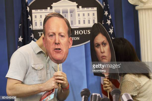 Attendees hold cardboard faces of Sean Spicer outgoing White House press secretary left and Sarah Huckabee Sanders White House press...