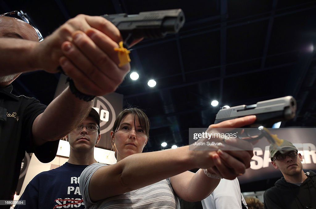 Attendees hold handguns in the Sig Sauer booth during the 2013 NRA Annual Meeting and Exhibits at the George R. Brown Convention Center on May 4, 2013 in Houston, Texas. More than 70,000 peope are expected to attend the NRA's 3-day annual meeting that features nearly 550 exhibitors, gun trade show and a political rally. The Show runs from May 3-5.