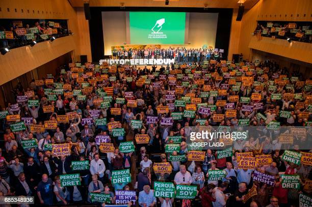 Attendees hold posters reading 'Because I'm democrat' and 'Because it's my right' during a political rally supporting a referendum on independence at...