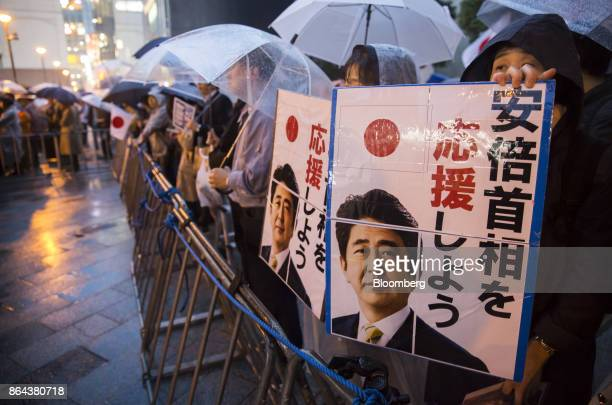 Attendees hold posters showing Shinzo Abe Japan's prime minister and president of the Liberal Democratic Party during an election campaign rally in...