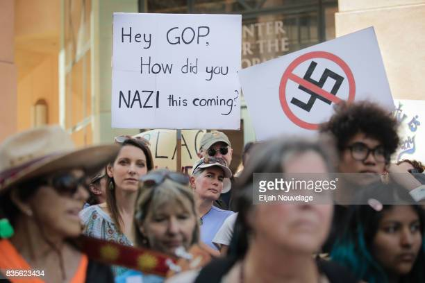 Attendees hold signs protesting Pres Donald Trump and the GOP at a rally against white nationalism on August 19 2017 in Mountain View California Just...