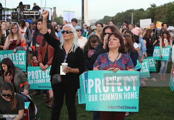 Attendees hold signs while listening to a speaker during the Moral Action on Climate Justice rally on the National Mall in Washington DC US on...