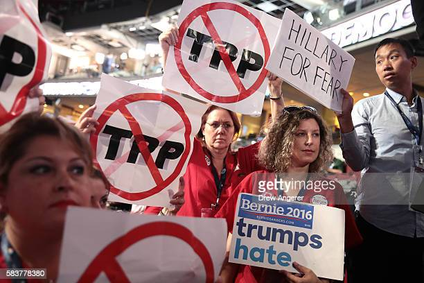 Attendees hold up signs that read 'TransPacific Partnership ' 'Hillary For Her' and 'Bernie trumps hate' on the third day of the Democratic National...