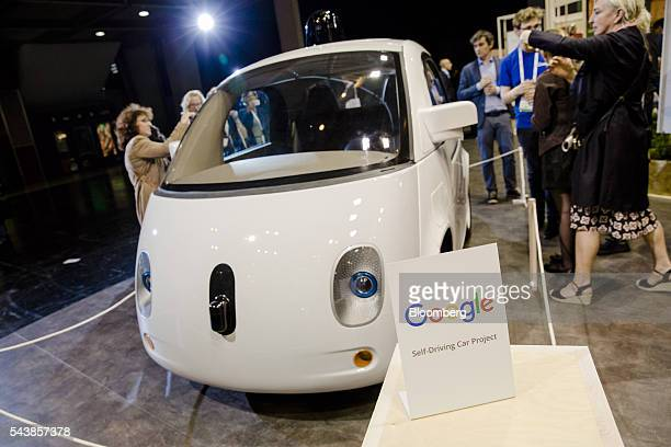 Attendees inspect a Google Inc selfdriving car at Viva Technology conference in Paris France on Thursday June 30 2016 The first edition of the new...
