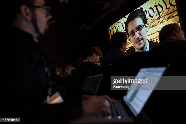 Attendees listen as Edward Snowden the former National Security Agency contractor speaks on screen during a virtual conversation at a featured...