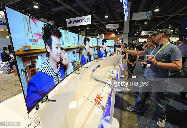 Attendees look at 65inch Skyworth 4K curved OLED televisions on display at the 2015 International CES at the Las Vegas Convention Center on January 8...