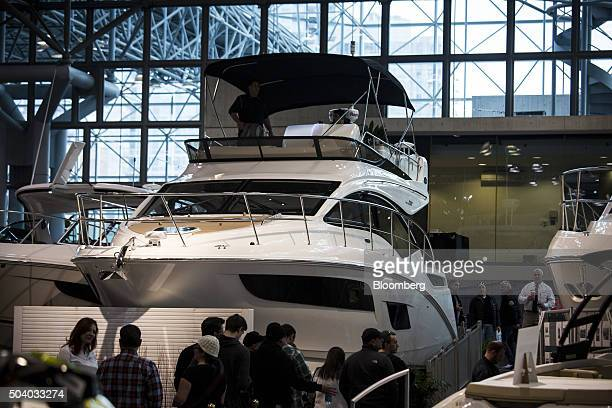 Attendees look at a 2016 Sea Ray 21 yacht at the New York Boat Show inside the Jacob Javits Convention Center in New York US on Friday Jan 8 2016 The...