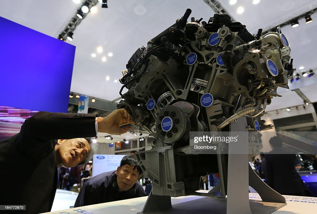 Attendees look at a 3.5L Ecoboost V6 engine displayed at the Ford Motor Co. booth during the press day of the Seoul Motor Show in Goyang, South Korea, on Thursday, March 28, 2013. The show runs from today until April 7. Photographer: SeongJoon Cho/Bloomberg via Getty Images