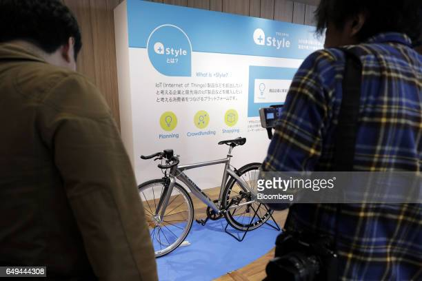 Attendees look at a CycleLabs Solutions Inc SmartHalo smart biking device attached to the handlebars of a bicycle at a SoftBank Corp Style media...