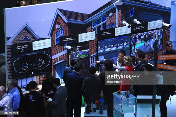 Attendees look at a display of smart campus solutions including facial recognition technology and intelligent video analysis in the Huawei...