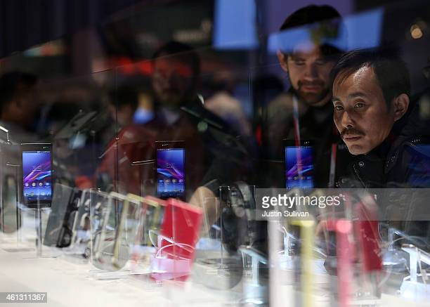 Attendees look at a display of the Sony Xperia Z1 compact smartphone in the Sony booth at the 2014 International CES at the Las Vegas Convention...