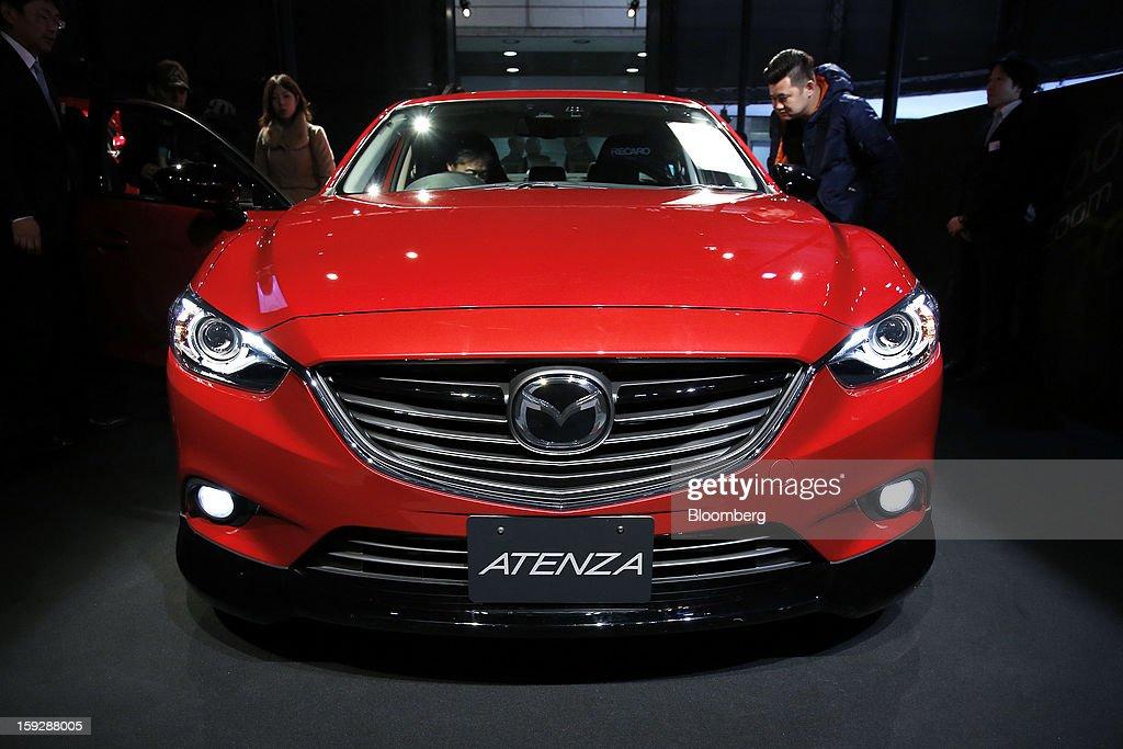 Attendees look at a Mazda Motor Corp. 2013 Mazda Atenza Racer displayed at the Tokyo Auto Salon 2013 at Makuhari Messe in Chiba, Japan, on Friday, Jan. 11, 2013. The Tokyo Auto Salon runs until Jan. 13. Photographer: Kiyoshi Ota/Bloomberg via Getty Images