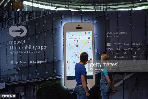Attendees look at a model smartphone displaying Daimler AG's Moovel mobility navigation app during Daimler's TecDay Road to the Future event in...