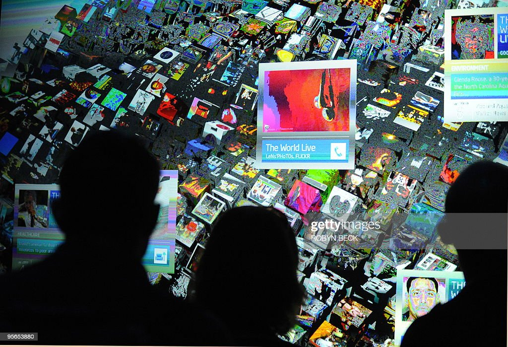 Attendees look at a myriad of internet content provided by a computer powered by the new Intel Core i7 processor on a prototype optical touch rear projection double high screen at the Intel booth at the 2010 International Consumer Electronics Show on January 8, 2010 in Las Vegas. CES, the world's largest annual consumer technology tradeshow, runs from January 7-10. AFP PHOTO/Robyn Beck