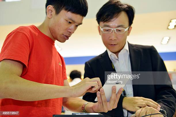 Attendees look at a Nokia OYJ Lumia 1020 smartphone during the Computex Taipei 2014 expo at the Taipei Nangang Exhibition Center in Taipei Taiwan on...