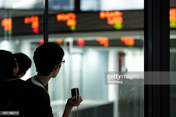 Attendees look at a stock ticker as they tour the Tokyo Stock Exchange Arrows facility during a parentandchild investment class hosted by Japan...