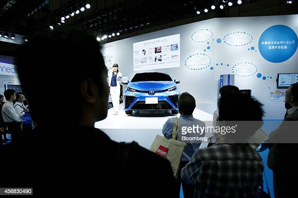 Attendees look at a Toyota Motor Corp fuelcell vehicle on display at the CuttingEdge IT Electronics Comprehensive Exhibition in Chiba Japan on...