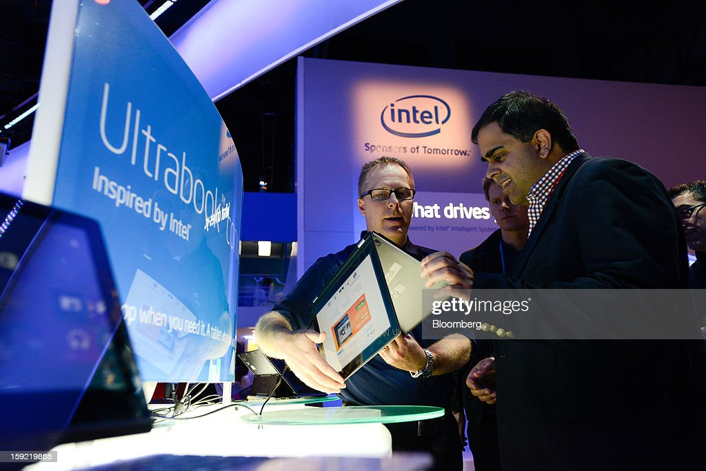 Attendees look at an Intel Corp. Ultrabook laptop at the company's booth at the 2013 Consumer Electronics Show in Las Vegas, Nevada, U.S., on Wednesday, Jan. 9, 2013. The 2013 CES trade show, which runs until Jan. 11, is the world's largest annual innovation event that offers an array of entrepreneur focused exhibits, events and conference sessions for technology entrepreneurs. Photographer: David Paul Morris/Bloomberg via Getty Images