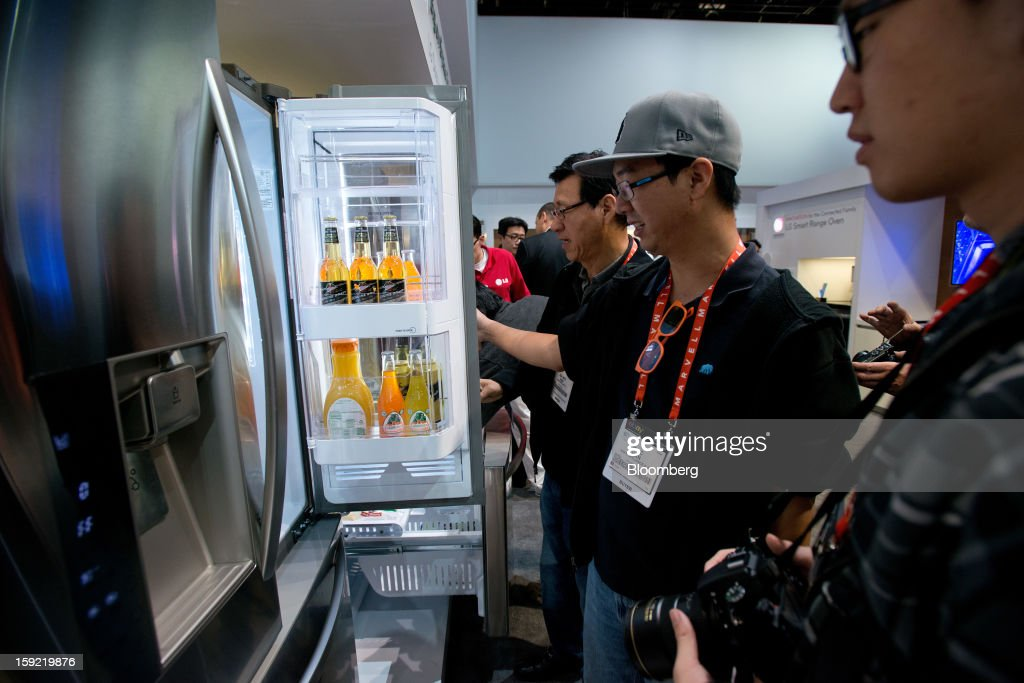 Attendees look at an LG Electronics Inc. refrigerator at the 2013 Consumer Electronics Show in Las Vegas, Nevada, U.S., on Wednesday, Jan. 9, 2013. The 2013 CES trade show, which runs until Jan. 11, is the world's largest annual innovation event that offers an array of entrepreneur focused exhibits, events and conference sessions for technology entrepreneurs. Photographer: David Paul Morris/Bloomberg via Getty Images