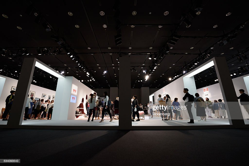 Attendees look at clothing items displayed during a preview of Fast Retailing Co.'s Uniqlo 2016 Fall-Winter lineup in Tokyo, Japan, on Wednesday, May 25, 2016. Analysts and investors will be watching as Uniqlo unveils the new season's LifeWear line in Tokyo to see whether Chairman Tadashi Yanai will come through with his pledge to offer the 'lowest possible prices.' Photographer: Akio Kon/Bloomberg via Getty Images