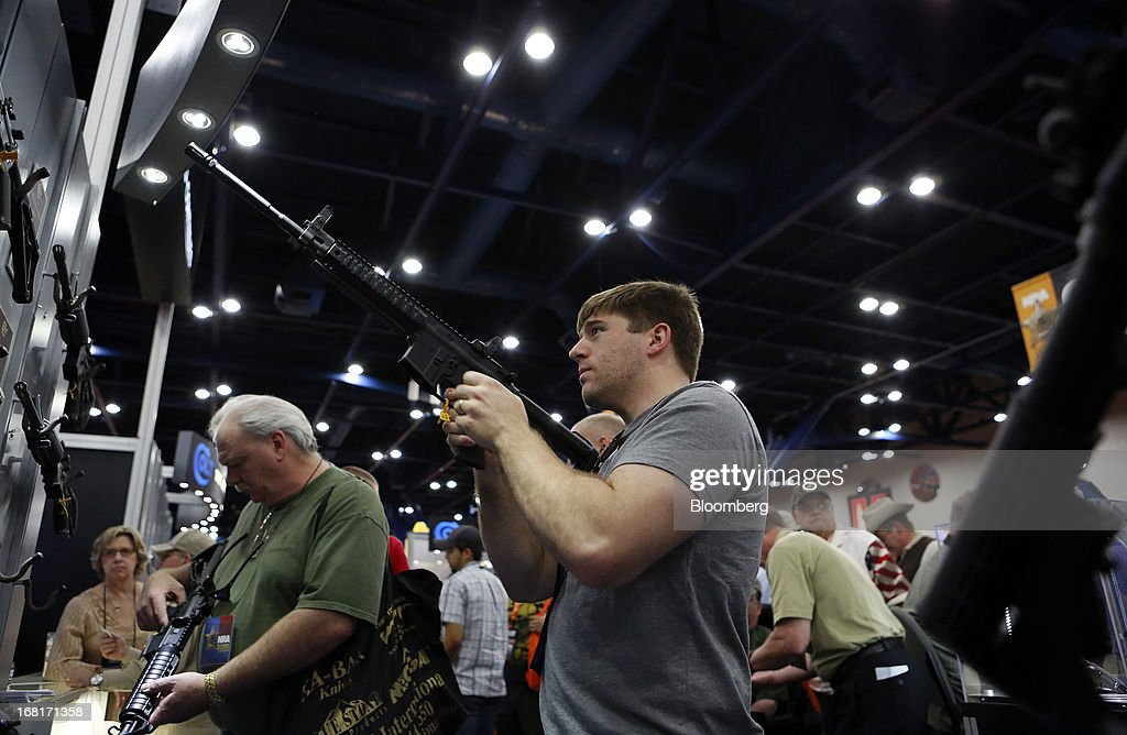 Attendees look at Colt Defense LLC rifles during the 2013 National Rifle Association (NRA) Annual Meetings & Exhibits at the George R. Brown Convention Center in Houston, Texas, U.S., on Saturday, May 4, 2013. After the U.S. Senate defeated a proposed expansion of background checks on gun purchases, the annual conference of the National Rifle Association in Houston has a celebratory atmosphere. Yet as the festivities began, gun-control advocates swarmed town halls, organizing petitions and buying local ads to pressure senators from Alaska to New Hampshire to reconsider the measure that failed by six votes on April 17. Photographer: Aaron M. Sprecher/Bloomberg via Getty Images