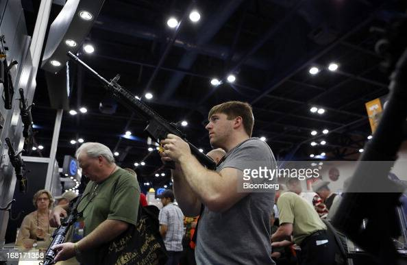 Attendees look at Colt Defense LLC rifles during the 2013 National Rifle Association Annual Meetings Exhibits at the George R Brown Convention Center...