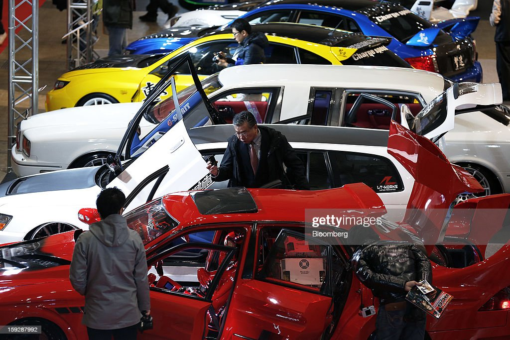 Attendees look at customized cars on display at the Tokyo Auto Salon 2013 at Makuhari Messe in Chiba, Japan, on Friday, Jan. 11, 2013. The Tokyo Auto Salon runs until Jan. 13. Photographer: Kiyoshi Ota/Bloomberg via Getty Images