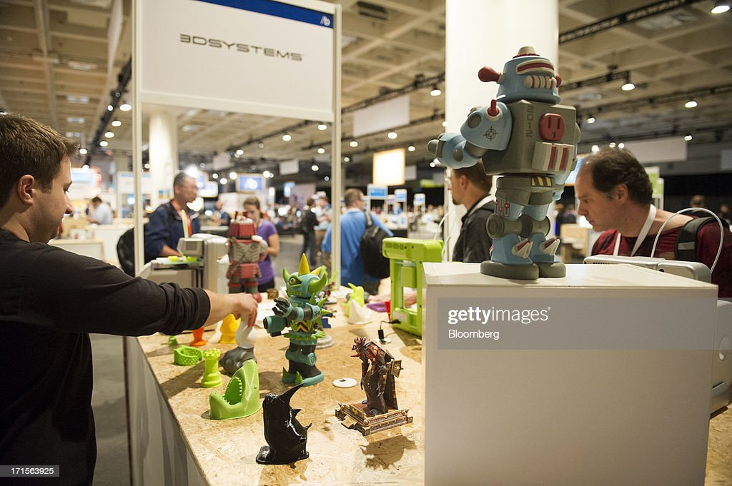 Attendees look at models created with 3D printers during the Microsoft Corp. Build Developers Conference in San Francisco, California, U.S., on Wednesday, June 26, 2013. Facebook Inc. is building an application for Microsoft Corp.'s Windows 8, adding one of the most popular programs still missing from the operating system designed to help Microsoft gain tablet customers. Photographer: David Paul Morris/Bloomberg via Getty Images
