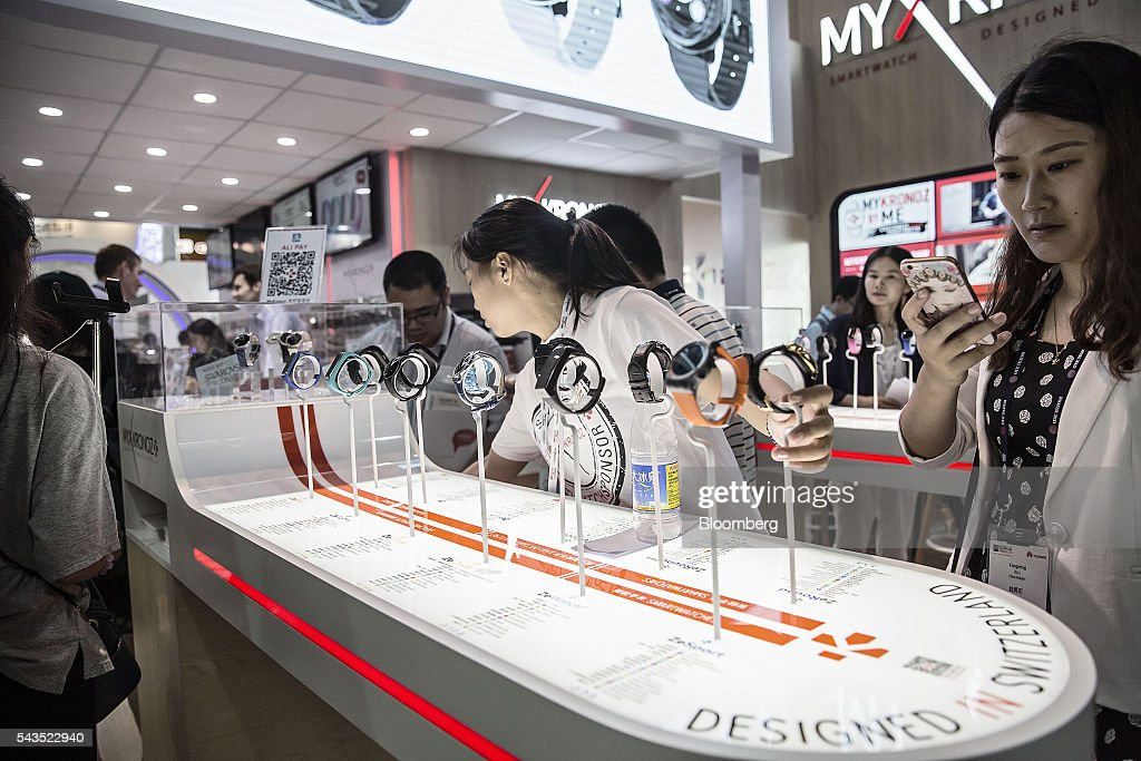 Attendees look at MyKronoz smartwatches manufactured by Kronoz LLC at the Mobile World Congress Shanghai in Shanghai, China, on Wednesday, June 29, 2016. The exhibition runs until July 1. Photographer: Qilai Shen/Bloomberg via Getty Images