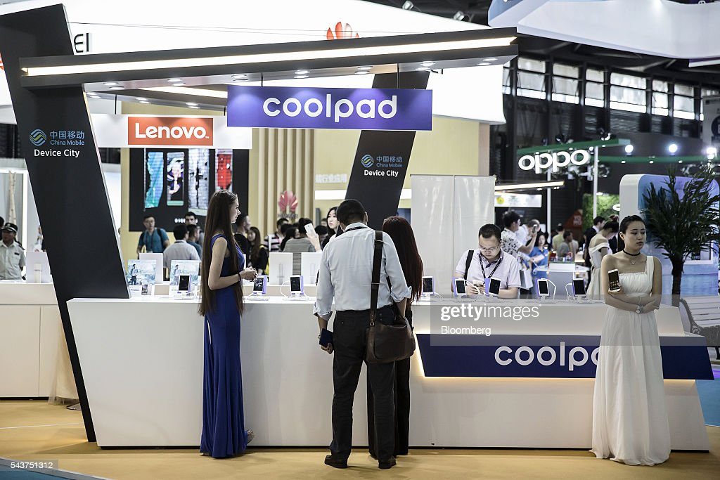 Attendees look at smartphones manufactured by Lenovo Group Ltd at the company's booth at the Mobile World Congress Shanghai in Shanghai China on...