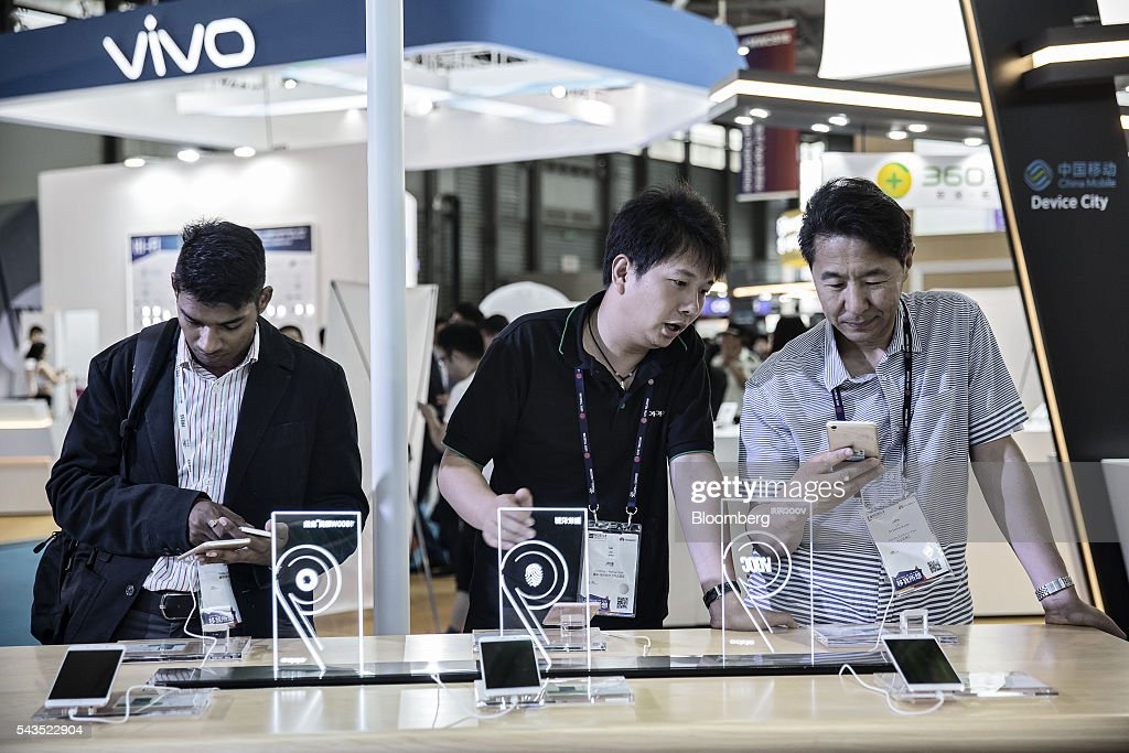 Attendees look at smartphones manufactured by Oppo at the Mobile World Congress Shanghai in Shanghai, China, on Wednesday, June 29, 2016. The exhibition runs until July 1. Photographer: Qilai Shen/Bloomberg via Getty Images