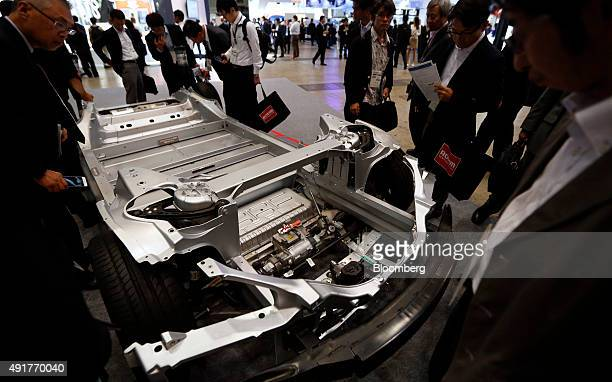 Attendees look at the chassis of a Tesla Model S vehicle manufactured by Tesla Motors Inc at the CuttingEdge IT Electronics Comprehensive Exhibition...