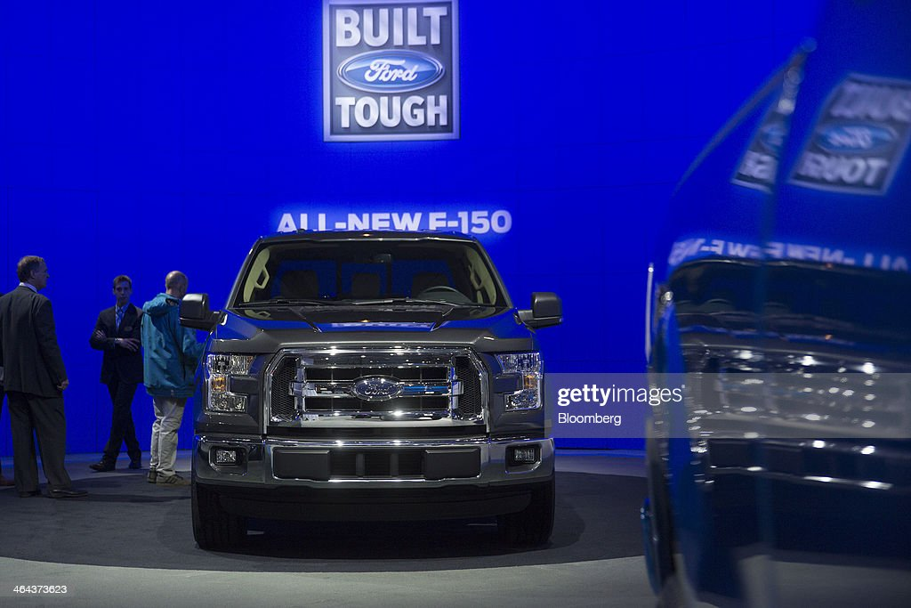 Attendees look at the Ford Motor Co. F-150 pickup truck during the Washington Auto Show in Washington, D.C., U.S., on Wednesday, Jan. 22, 2014. After laboring for five years to develop its aluminum F-150, Ford Motor Co. now confronts a new challenge: preventing higher insurance rates and a dearth of mechanics equipped to repair its body from deterring buyers. Photographer: Andrew Harrer/Bloomberg via Getty Images